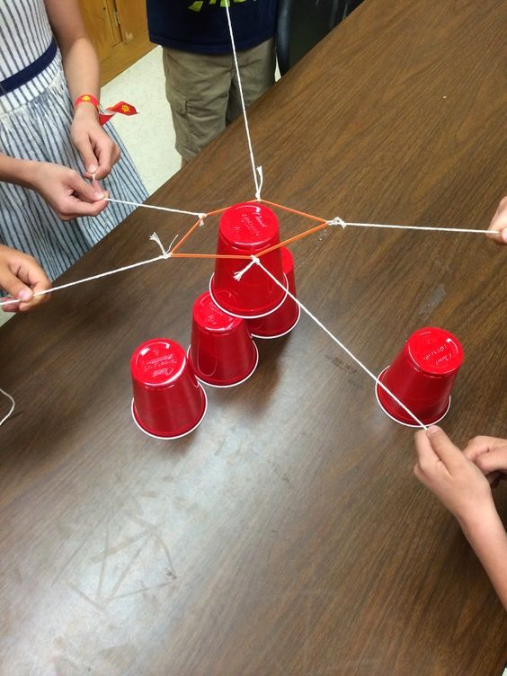 Build a tower of cups together using an elastic band with several strings attached. The cups may not be touched.
