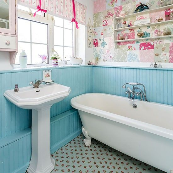 Country bathroom with painted panelling. Painted wood panelling and a patchwork of wallpapers adds character to this vintage-style bathroom with roll-top bath.