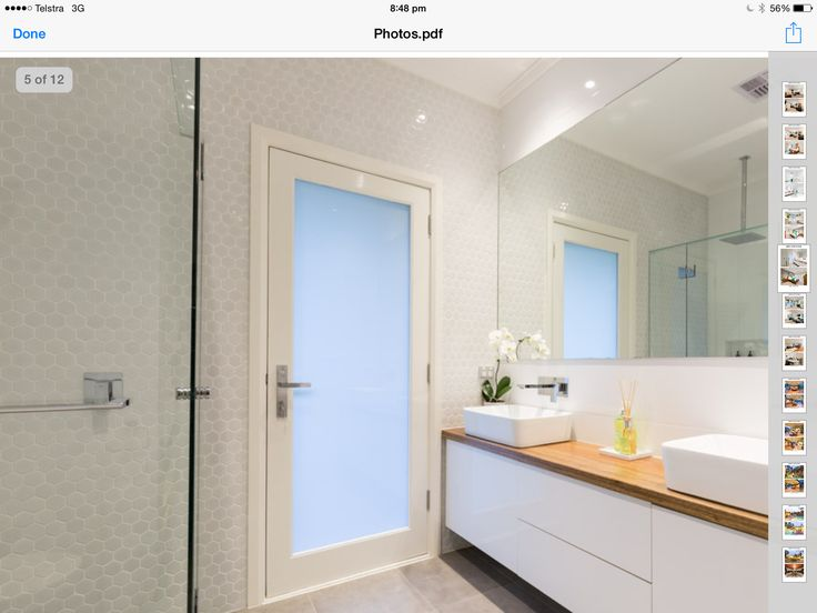 Onsuite small white hex tiles adds interest to a neutral white grey bathroom and warmth with recycled wood tops