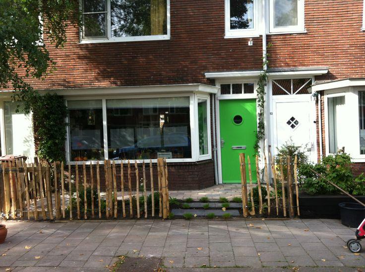 De voortuin bepaald de uitstraling van het huis. Hier is, ondanks de kleine ruimte, gekozen voor zo veel mogelijk groen, met een kastanje hekje.