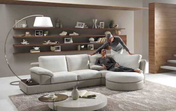 Amazing living room interior design ideas with gray wall and wood shelves decoration also classic curved style free standing round lighting complete l shaped sofa soft sponge fabric use cushion that have two rounded table marble and gloss material decor using carpeted flooring idea