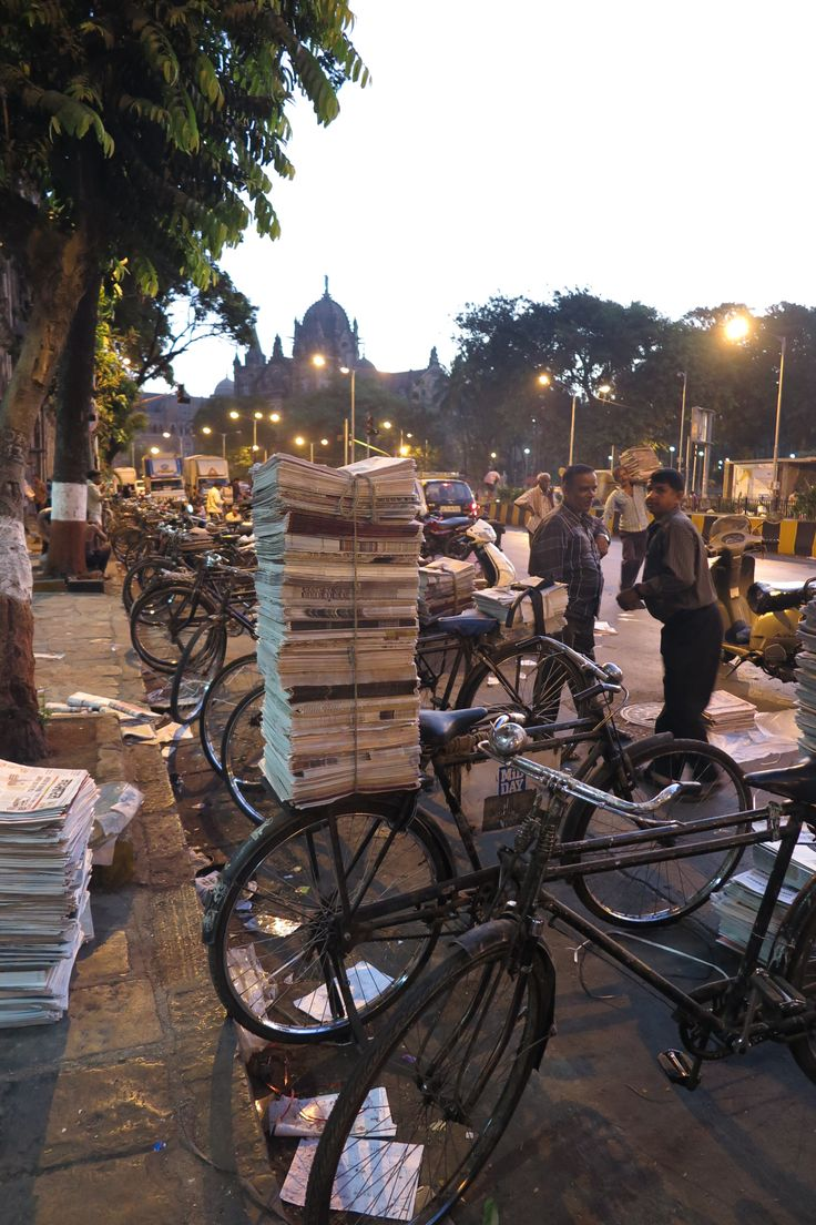 Early morning paper workers as the sun comes up over the train station in the background. Shared a coffee with them as they sorted papers in 30 different languages and then loaded them up for delivery.