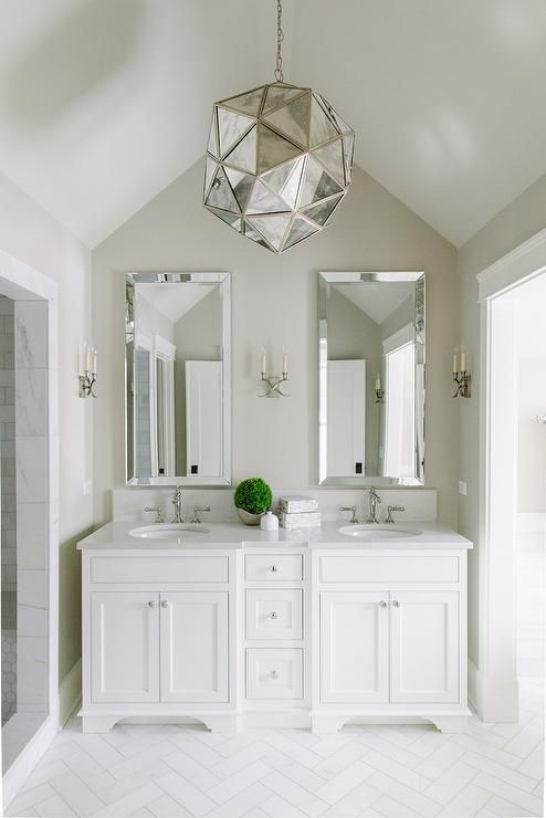 Charming White And Tan Bathroom Boasts An Antiqued Mirrored Light Pendant Hung From A Vaulted Ceiling Over White Herringbone Marble Floor Tiles Leading To A