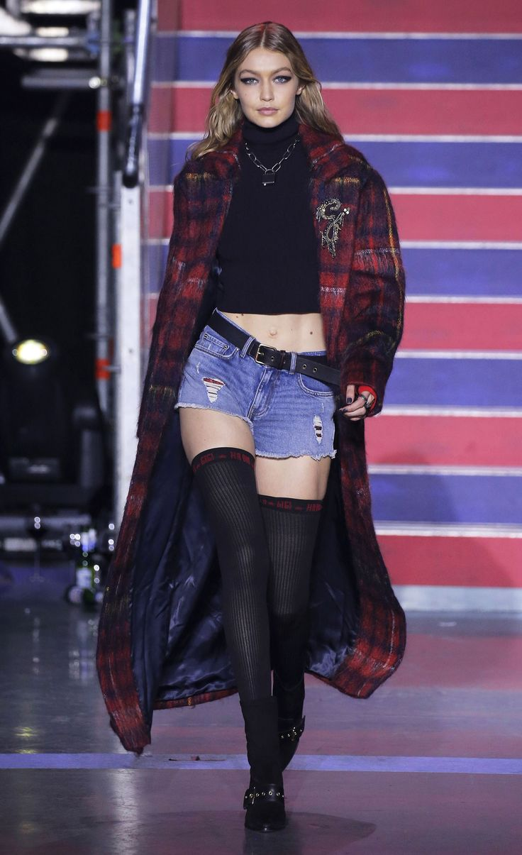 Gigi Hadid opens the Fall 2017 TOMMYNOW show in London wearing the Gigi Hadid Mohair Wool Coat, Gigi Hadid Cropped Poloneck Sweater, Gigi Hadid Distressed Denim Shorts, and accessories, all from the new TOMMYXGIGI collection.