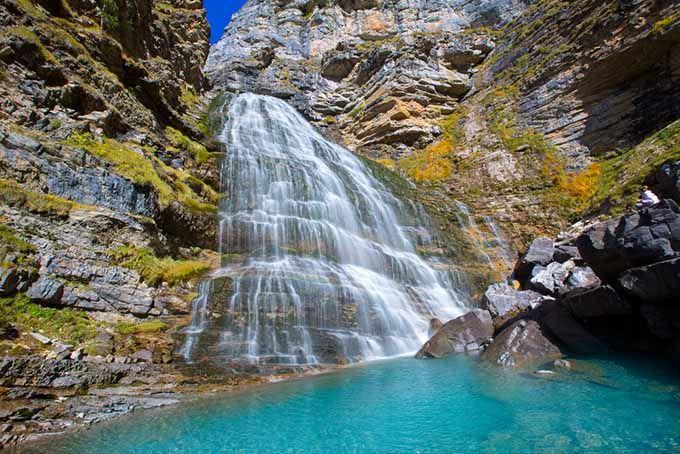 COLA DE CABALLO – Huesca – España El Valle de Ordesa, en el Pirineo Aragonés, es un espectáculo de la naturaleza perfecto para una escapada. Dentro del Parque Nacional de Ordesa y Monte Perdido, una de las excursiones más populares es la que lleva hasta la Cola de Caballo, una cascada espectacular que se abre en un abanico blanco y que se desliza roca abajo