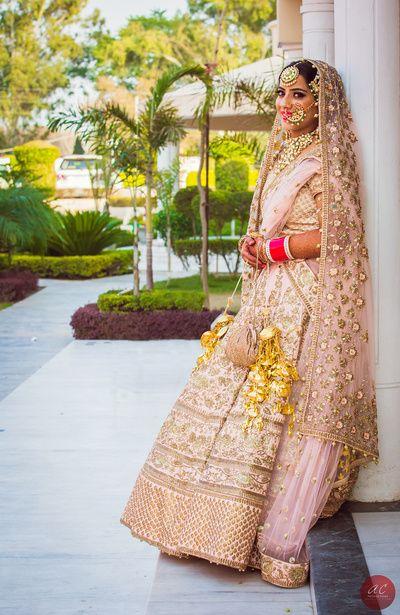 light blush pink heavy ornate bridal lehenga with gorgeous jewellery and jewelled nosering #wedmegood