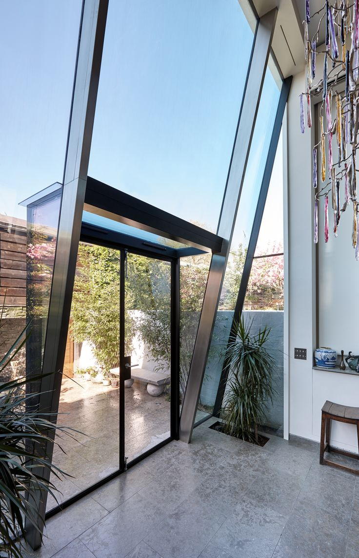 Trombe - Internal photo showing the mini shard style of the double height structurally glazed lean to extension. The internal side of the inclined steel rafters have been clad with stainless steel pressings.
