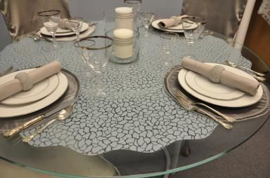 Use Wallpaper For Windows static cling film on you glass table tops.  It's great to create a decorative cover  hide scratches in the glass.