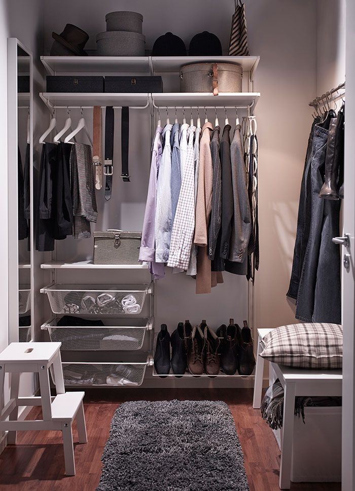 A small walk-in-closet with white wall shelves, clothes rails, mesh baskets and shoe shelf