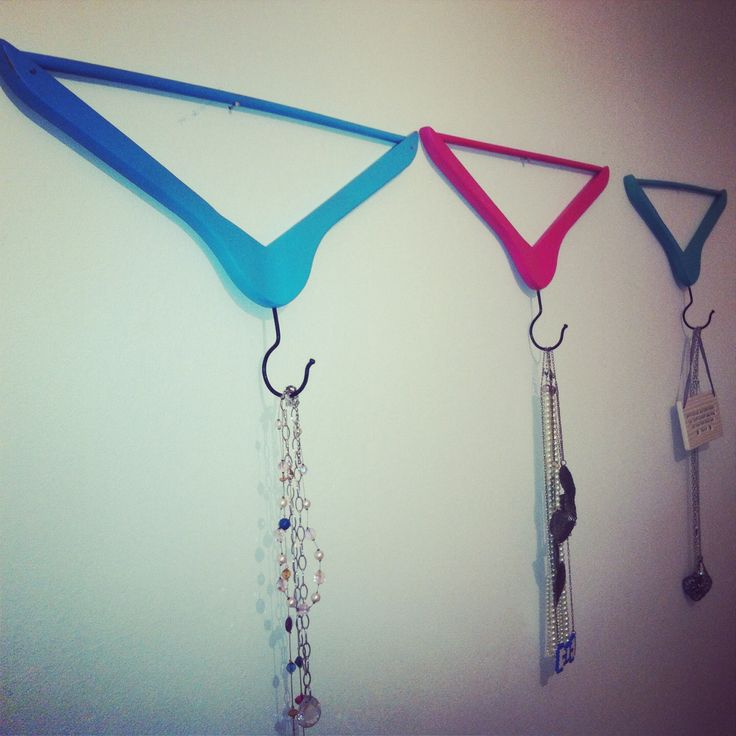 Wooden hangers sprayed in different colours and used upside down as hooks on a wall.