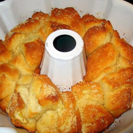 GARLIC PARMESAN PULL-APART BREAD 1 can of refrigerated Grands biscuits ½ stick of butter 3 cloves of garlic, minced ½ cup grated Parmesan cheese