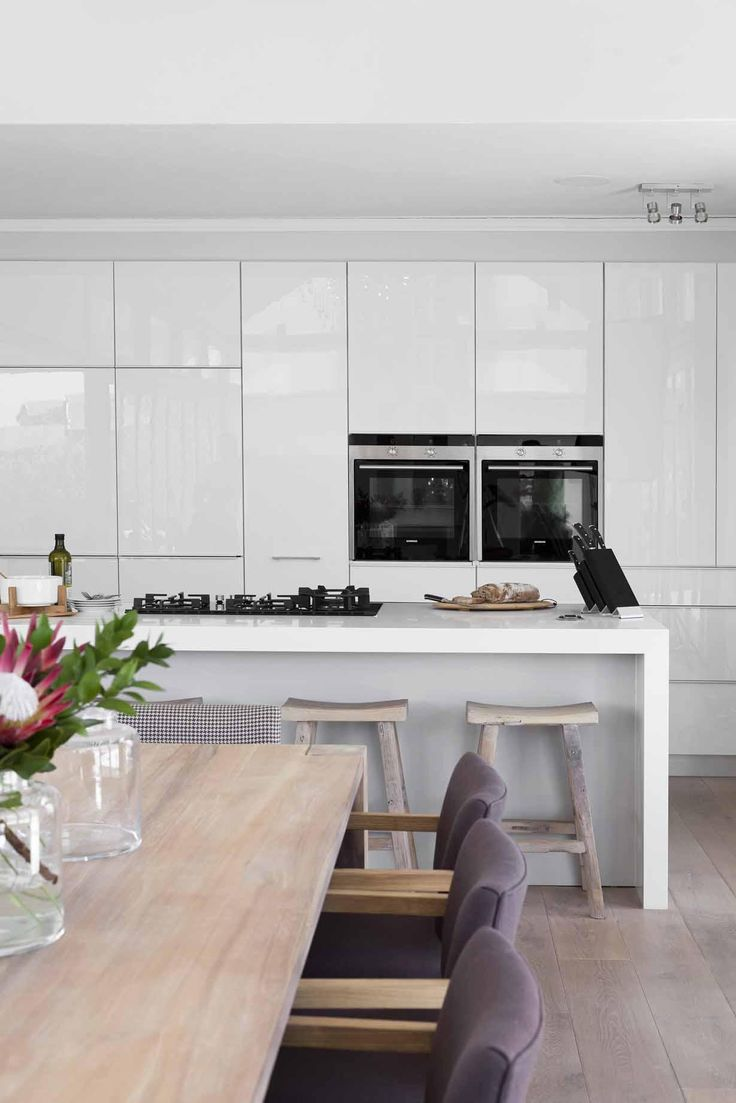 Minimalist White Kitchen Juxtaposed Against The Natural Elements Of Dining Room