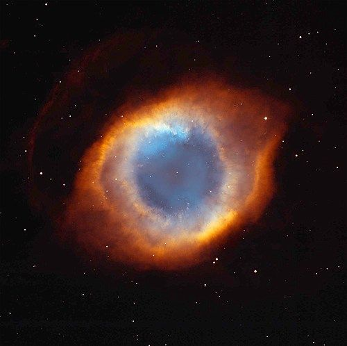 "This image of the coil-shaped Helix Nebula (also known as ""The Eye of God"") is a composite of images from the Hubble Space Telescope and from the Mosaic Camera on the National Science Foundation's 0.9-meter telescope at Kitt Peak National Observatory near Tucson, Ariz."