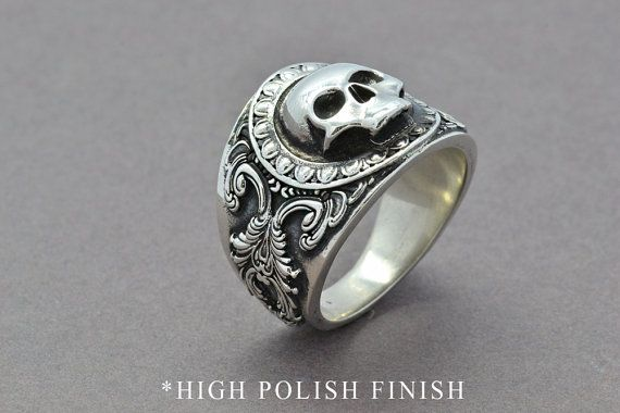 The Reaper Ring was designed as a statement piece with a comfort fit, ideal for every day wear! A custom made to order comfort fit ring featuring a 3 dimensional Skull face and scroll pattern made in high quality tarnish-resistant Sterling Silver. This ring makes for a great groomsman gift, graduation, birthday or anniversary gift! ADDITIONAL INFORMATION: Band: 5.8mm (at back) Front Width: 21.5mm Material: High quality tarnish-resistant Sterling Silver with an oxidizing agent for the…
