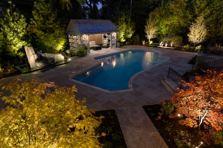 A new pavilion and nine massive white pine trees greatly increased privacy in this backyard.  Rectangular flagstone surrounds the pool, while statuary and the granite water feature provide focal points amongst the gardens. A stunning bit of landscape lighting sets off each feature beautifully.