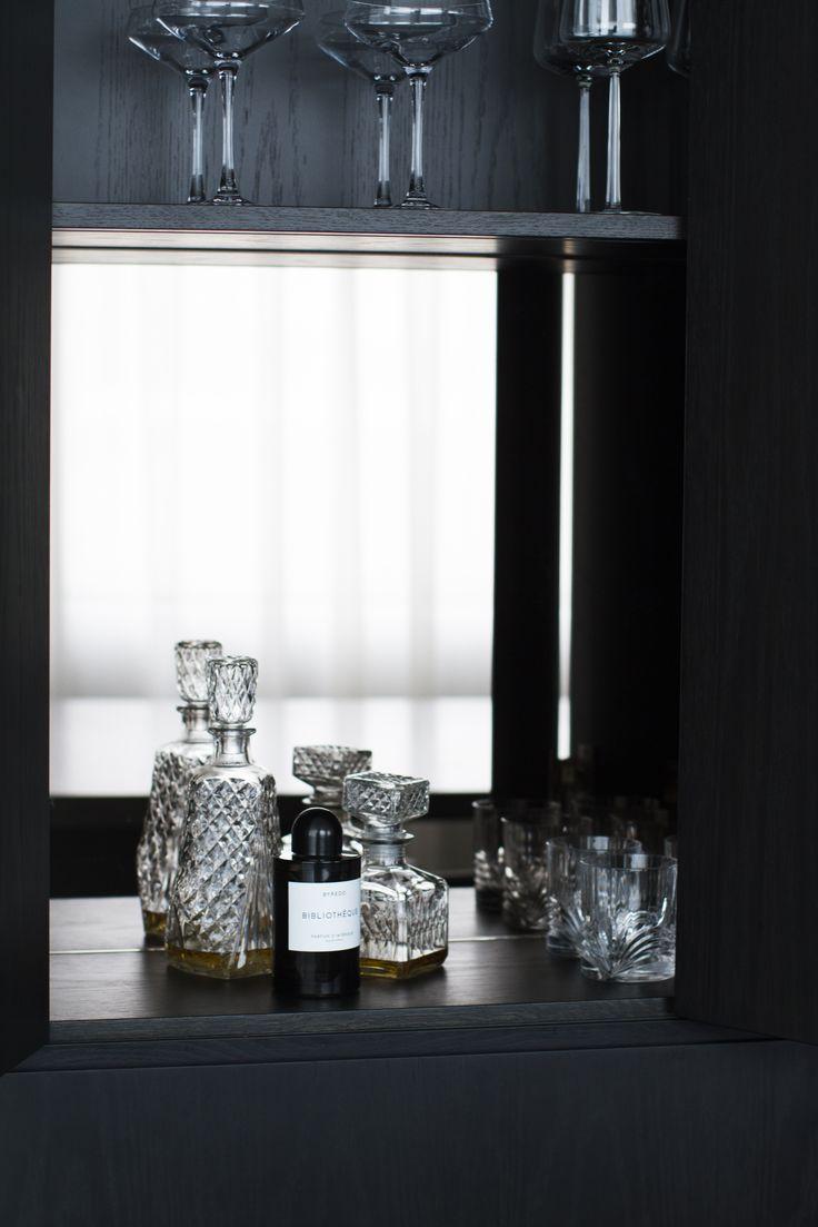 Hidden bar in a stained oak kitchen with bronze mirror splash back. Designed by Sæja interior designer.