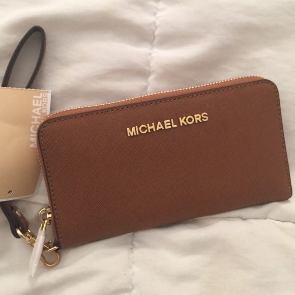 """MICHAEL KORS WALLET Brand new - jet set travel collection . Color : luggage / brown. Size : large. Saffiano Leather  -Compatible with iPhone 4, iPhone 5, iPhone 6 and Samsung Galaxy  -Top Handle: 7""""  -Interior: One Zip Coin Pocket, One Cell Phone Pocket, Three Card Holders, One Open Pocket  -6.5 X 3.75 X 1""""  -Top Zip MICHAEL Michael Kors Bags Wallets"""