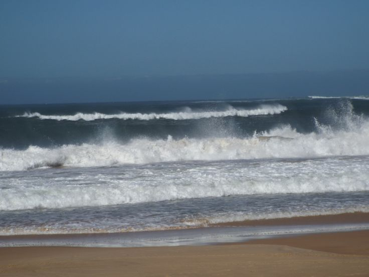 Water and sand flying from the messy wave action and wind
