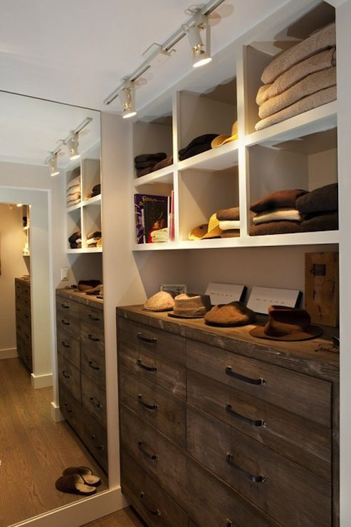 Fantastic walk-in closet with track lighting, floor mirror, rustic chest of drawers in an antique finish and white built-ins. Two please...one for me and one for the messy hubby.