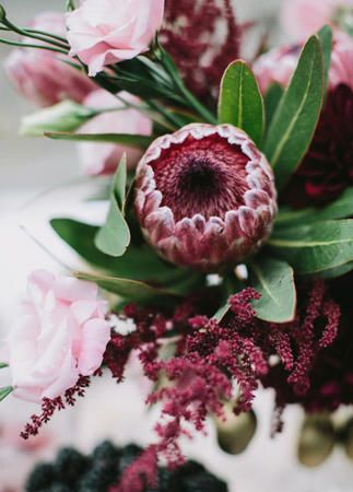 Burgundy King Protea Centerpiece: The new hot flower of the desert wedding trend, protea are flowers that traditionally come from arid climates and bloom in the fall. It's a beautiful statement bloom for a bridal bouquet or fun as the focus of a small centerpiece display.