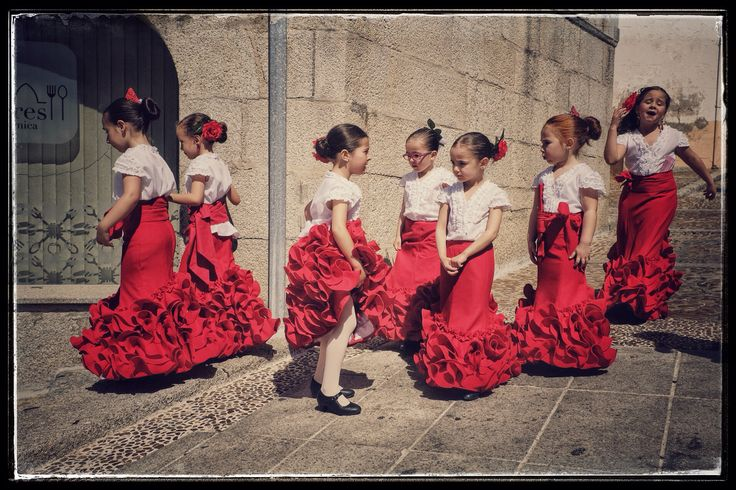 Esta es una foto do niñas vestidas para bailar el Flamenco. Esto es un baile que origino en España hace muchos siglos. Este baile es muy comun y tradicional. El estilo de baile es muy expresivo y apasionado que involucra muchas emociones.