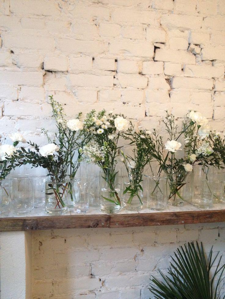 en velgg av hvite blomster i vaser som utstilling