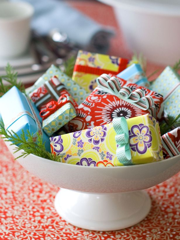 A basket of beautifully-wrapped gifts serves two purposes: It's a bright, festive table centerpiece and a source of treats for unexpected guests. http://www.hgtv.com/entertaining/dress-your-dining-room-for-the-holidays/pictures/page-11.html?soc=hpp
