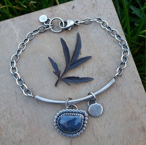 A 7 long sterling silver bracelet with a blue sapphire gemstone and two nuggets of silver. The clasp can be fixed at any point along the chain to make the bracelet fit tighter. The bracelet has my logo and an authentic London Assay Office hallmark with my personal makers mark (this