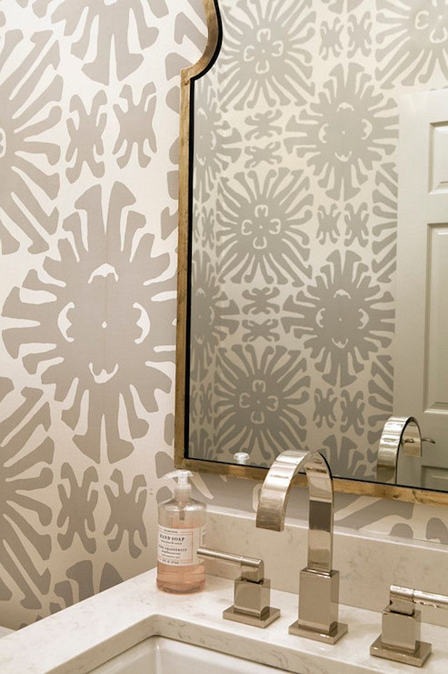 Beautiful powder room features walls clad in white and gray wallpaper. http://lelandswallpaper.com