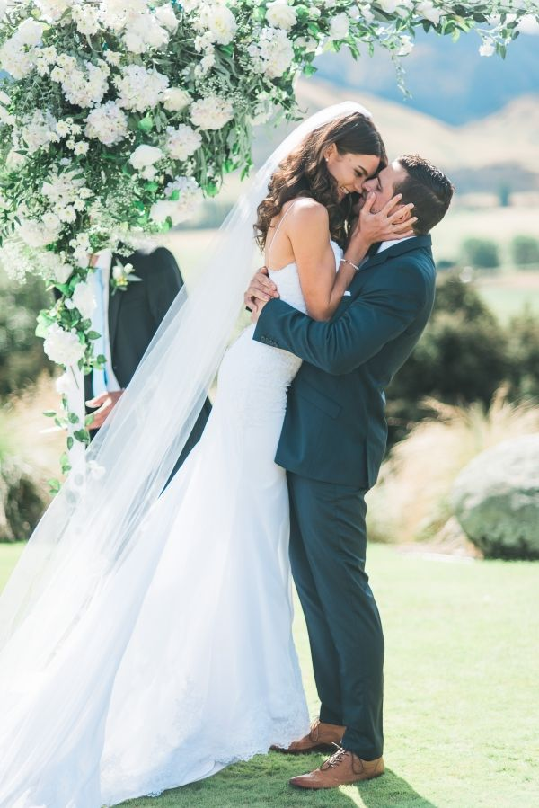 First Kiss under a Green and White Wedding Ceremony Arch | Nordica Photography on @fabyoubliss via @aislesociety