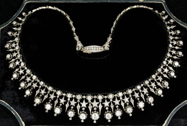 This stunning late Victorian diamond necklace, which comprises no fewer than 78 old-cut stones graduating in size with a total diamond weight of 12cts and suspended in a gold and silver fringe setting. It still retains its green Morocco leather gilt and red tooled fitted case.