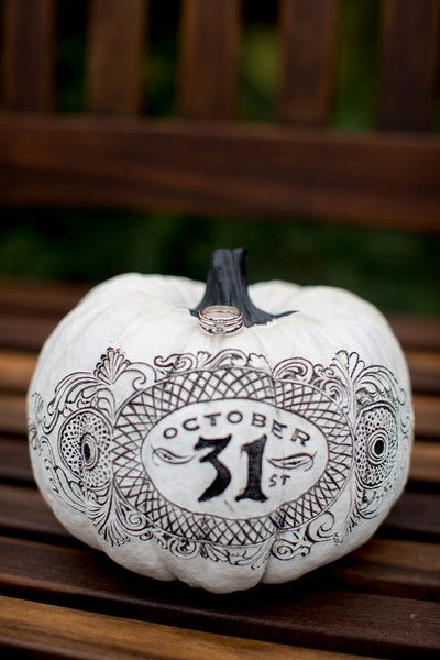 """Halloween-themed pumpkin wedding decor idea - white pumpkin with black designs with """"October 31st"""" written on it and engagement rings [Amy E Photography}"""