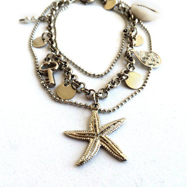 Tornozeleira tripla de metal prateado. Duas são correntes de bolinhas e uma corrente com pingentes de estrela do mar, miçanga perolada, búzio e medalhinhas....