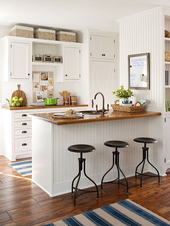 Such a sweet little country kitchen.  Love the wood countertops, beadboard, barstools, the drawer pulls, and the shaker cabinets.