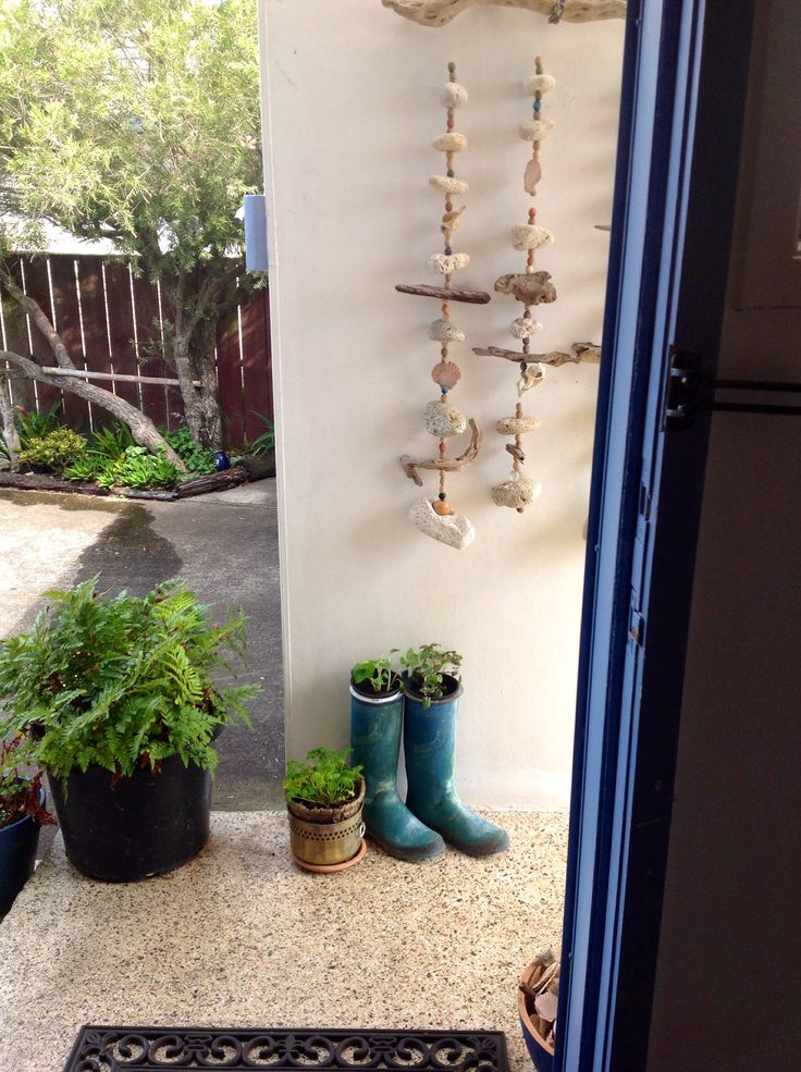 Front door - plants in gumboots and shell and driftwood hanging on the wall