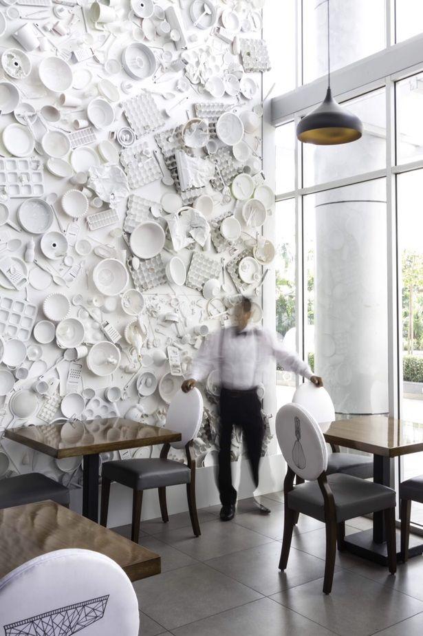 Pared de restaurante decorada con vajilla. Dyanon Bistro | Jannina Cabal | Archinect