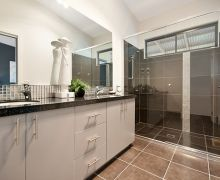 Dark floor tile continued through large shower with vertical feature tile.