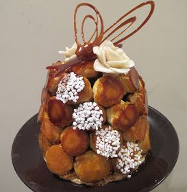 - Socle en nougatine  - Choux caramélisés fourrés à la crèmepâtissièrevanillés  - Roses en pâte d'amande  - Décor en caramel