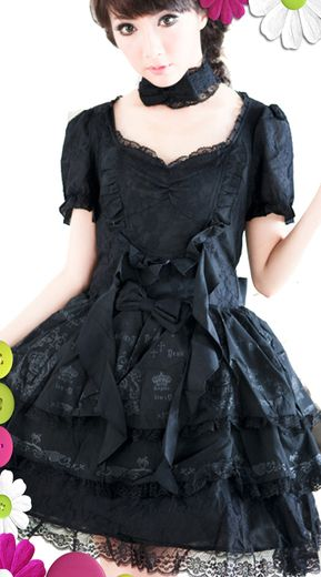 """An all black gothic lolita dress that is layered and tiered in black lace.  The print on the skirt is crowns and crucifixes with the words """"Angels"""" and """"Devil"""".  Delicate bow to the waist and a large black bow to the rear.  Accompanying the dress is a black bowed choker."""