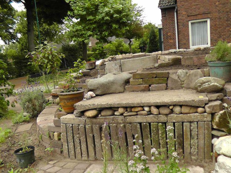 Tuinbank geïntegreerd in verhoogde kruidentuin van gestapelde stenen