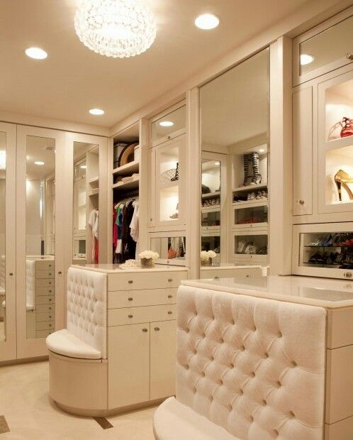 Great closet! The designer made good use of the side of the cabinets as seating, rather than adding bulky furniture. Clever way to keep it looking spacious!