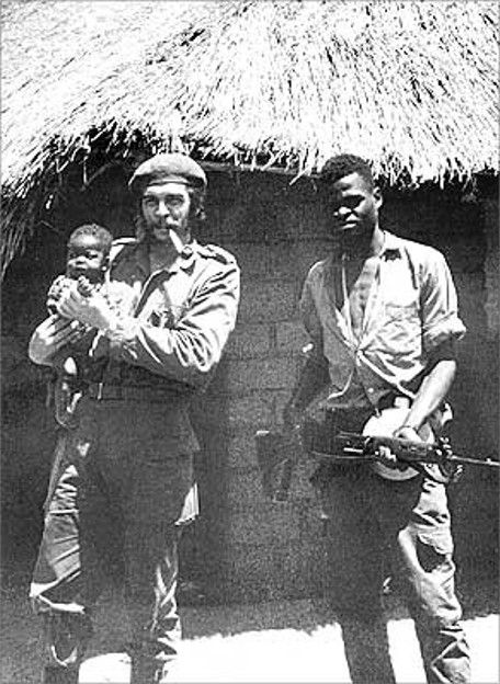 37-year-old Che Guevara, holding an African baby and standing with a fellow Cuban soldier during the Congo Crisis, 1965.  Source: Museo Che Guevara