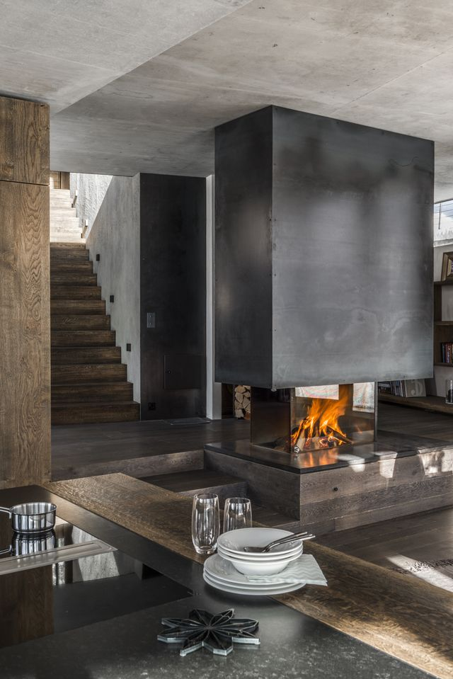 Both the dining table and the fireplace are bespoke designs by Gogl Architekten.