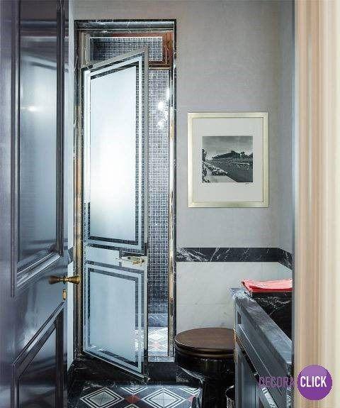 Decoração de Interiores – Banheiros  Projeto: Steven Gambrel. A porta ao fundo parece uma porta de saída, mas é a porta de entrada para o banho. Elementos metálicos fazem o charme desta decoração que foge do convencional. O uso de pastilhas escuras combinadas ao piso preto e vermelho, com linhas geométricas, compõe uma decoração arrojada e incomum.   Veja mais no nosso Decora Blog!  http://decoraclick.com.br/decoracao-de-interiores-banheiros-35/