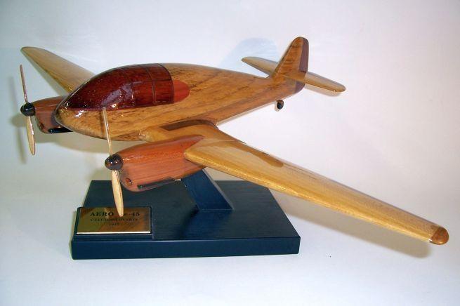 Model letadla ze dřeva ve vzletové poloze včetně stojánku s věnováním.  AERO Ae-45
