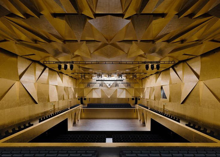 This concert hall features ribbed glass cladding and a spiky roof, giving it the appearance of an icy crown.