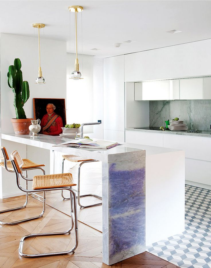 Artistic kitchen with white marble, cactus, industrial lights, and tiled floor