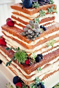 Wedding cake with exposed edges, succulents, plums, and forest berries.