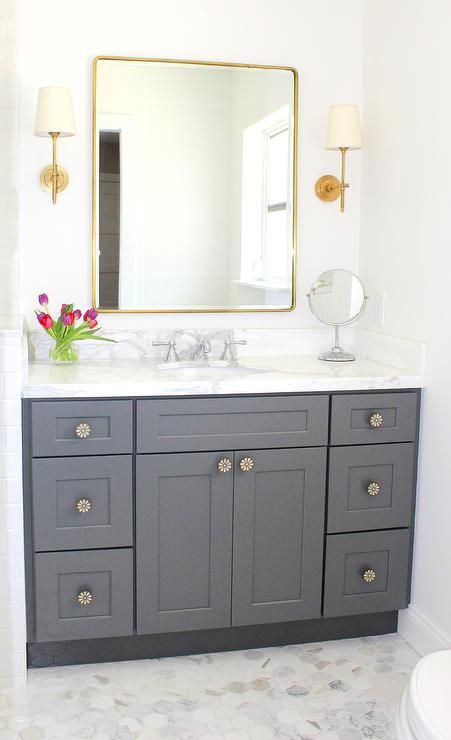 Traditional bathroom featuring gray shaker style cabinetry, marble hexagon…