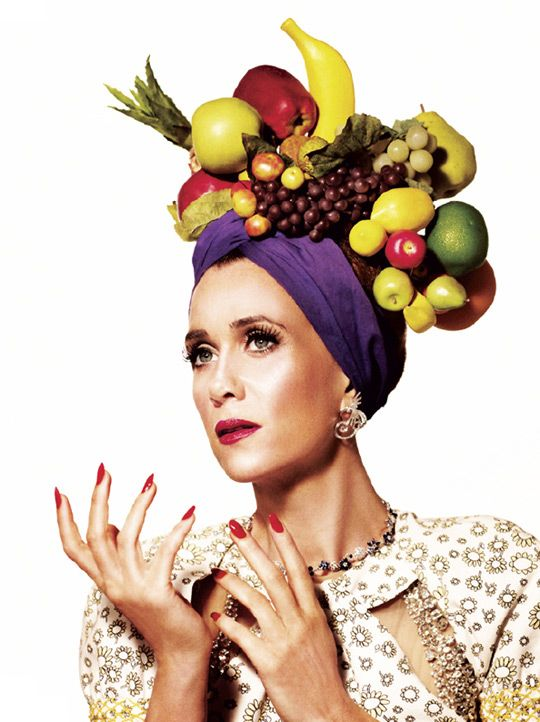 Kristen Wiig imitating entertainment icon Carmen Miranda in a turban bedecked with pineapple and other fruit.